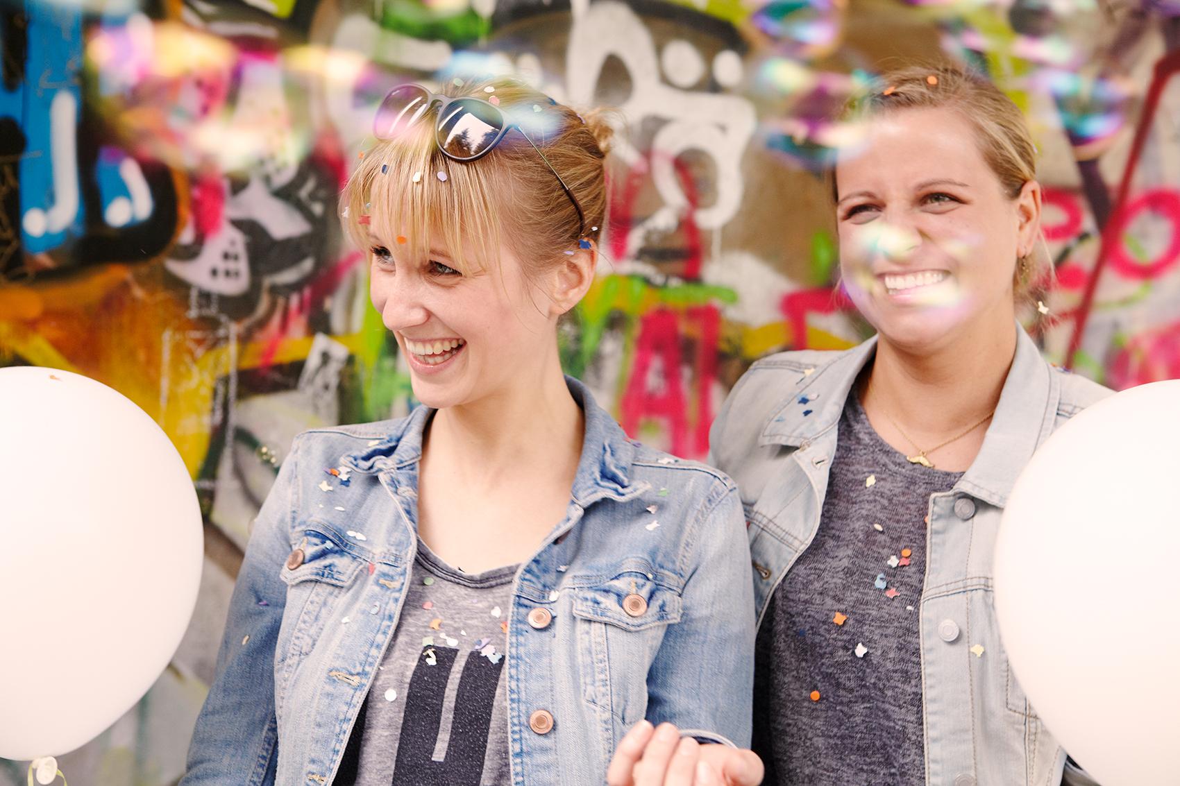 Ausgelassener Junggesellinenabschied im Park. Beste Freundinnen feiern mit Konfettiregen, Slackline, Luftballons, Luftblasen und zelebrieren ein wunderschönes Fest.
